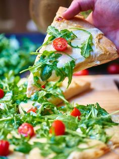Roasted Garlic White Cheese Pizza w/ Arugula Salad. A simple pizza loaded with a spicy white sauce, cheese, & topped w/ lemon arugula salad!