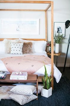 Pretty bedroom in white and blush pink tones and wood canopy bed