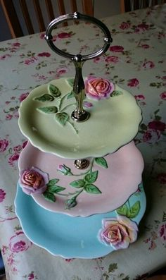 Pretty pastel 3-tier serving plates with roses on a vintage rosy tablecloth.