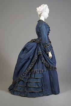 Daytime Dress 1870-1878      Dress is pleated and with fringed trimmings that are applied to the sleeves, the bodice and its elongated basques and to the skirt