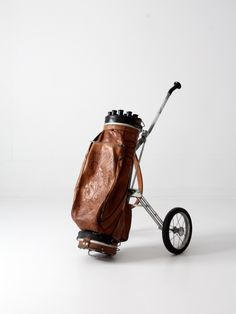circa 1950s A vintage tooled leather golf club bag with a vintage Ajay Playmate cart. The caramel leather bag features an Indian chief design. It features three pockets and a leather carrying strap. T