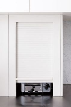 Hide everyday appliances, such as the toaster, in a cupboard with a retractable roller door.