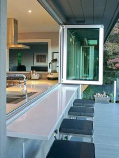 Kitchen with Huge Open Window for serving directly to the Outside Bar Area. Great Idea! Love the Pale Blue Patio/Bar Area. Pic # 2