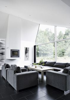 Nordic and stylish living room with grey couches. We love the big glass window whit a beautiful view.
