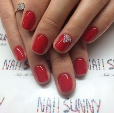 Perfect glossy red is decorated by a laconic pattern on the ring finger. Large transparent rhinestones, arranged in a triangle at the base of the nail are used in design. Reminding of gems, this finish gives a festive look to a casual red. This manicure is self-sufficient and should be worn with a minimal amount of jewellery.