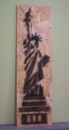 La statue de la Liberté revisitée, réalisée avec la technique du string art ou encore du fil tendu. Elle est sur un support en bois aggloméré de taille 32/120 des pointes en acier poli et du fil pour crochet noir. Elle peut être posée ou suspendue.