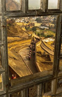 A view of Jaipur through a window, with elephants traveling along the pathway below...