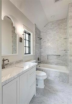 White carrera marble floors, tub surround and counters, antique nickel faucet, Toto toilet, recessed lighting and iron sconces. #bathroomfurniturewhitebathtubs