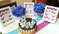 Table decoration and cake for baby shower in purple, blue and white.