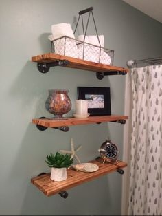 Very cool $60. DIY plumbing pipe & wood bathroom wall shelves Wall Paint color is Silvermist by Sherwin Williams. Cedar wood industrial shelving. Raindrops shower curtain from Target. Budget remodel!