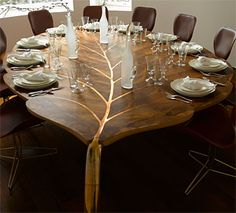 That's a dining room table with tons of potential. It would be an elegant addition to a formal dining room and equally perfect in a more whimsical room. I can even imagine it in a Hobbit house. :-) It's by John Makepeace Furniture Designs