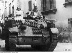 """""""Pchor. Edward Wojczak z 6 Pułku Pancernego """"Dzieci Lwowskich"""" jako Święty Mikołaj udaje się wraz z dziewczynką przebraną za aniołka, na czołgu M3/M5 Stuart, do dzieci w Bibbiena. 6 grudnia 1944 r."""""""
