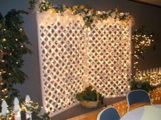 Lovely! Two panels of lattice hinged together and secured to a base or frame. Decorate with lots of clear lights, flowers, greenery, ribbon or tulle. http://moodstruck.com/clear-lights-50.html