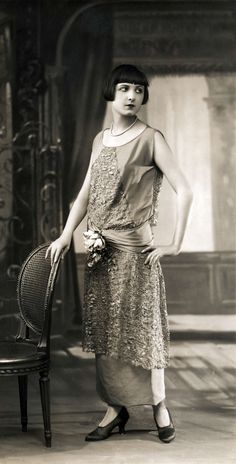 Women's Fashion. Fashion model shows off a dress to the ankles, consisting of two layers and a sash around the waist. Spring collection. No place, 1924.