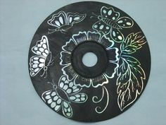 By painting a CD black and etching out a pattern, you can make beautiful wall art.