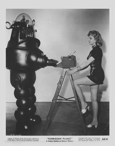 """Anne Francis (as Altaira """"Alta"""" Morbius) and Frankie Darro (stuntman inside """"Robby the Robot"""") in a publicity photo from the 1956 Metro-Goldwyn-Mayer film """"Forbidden Planet"""". Fiction Movies, Science Fiction Art, Fantasy Movies, Sci Fi Fantasy, Pinup, Great Sci Fi Movies, Z Movie, Movie Facts, Robby The Robot"""