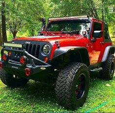 RED 2 DOOR JEEP SOFT TOP WITH CUSTOMIZED GRILL, RIMS, BUMBER , & LED LIGHTS & SNORKEL
