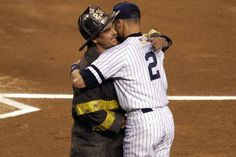 Derek Jeter of the New York Yankees embraces a New York City fire fighter during introductions prior to Game 1 of the American League Division Series against the Oakland Athletics on Oct. 10, 2001 at Yankee Stadium.