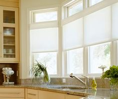 Visit this blog post for so many kitchen window treatments. I love this one!  Shear shades hung eye level in the window.  Perfect for blocking the sun but allowing light to still come in at the top level.