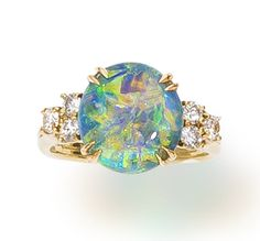 An opal and diamond ring, Harry Winston  centering an oval cabochon black opal, weighing 3.72 carats, with round brilliant-cut diamond three-stone shoulders and a fluted mount; signed Winston for Harry Winston