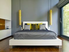 Grey and yellow are a cool colour combination and work well with the white bed, wooden floor and stunning view out the window. Bedroom by Baufritz (UK) Ltd.