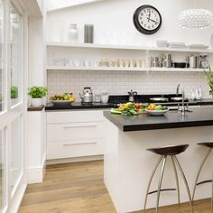 Black & white kitchen with open shelving - think white countertops work better. Good to see the cabinets against a wood floor