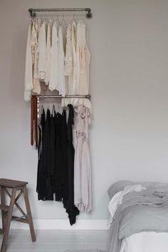 un vestidor improvisado con dos simples barras para colgar la ropa