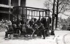 Rotterdam 1940/'45 - Bombardement van Rotterdam. Puinruimers zitten in en om een bushalte tijdens hun schaftuurtje, zij verrichten zware arbeid en dus mogen zij wel een extra broodbon hebben, Rotterdam, juni 1940.