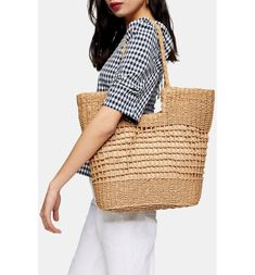 This contemporary take on a woven bag features open squares, a cutout shoulder opening and a roomy interior for a day by the sea.