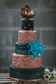 Black and Gold 5 Tiered Nautical Inspired Wedding Cake with Pirate Ship and Octopus Details | Ashlee Hamon Photography on /marrymetampabay/ via /aislesociety/