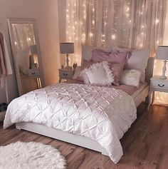 Fairy lights and white net curtains behind the bed. Lovely! That dusty pink accent is pretty too