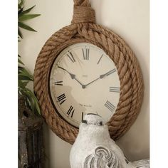 Rustic reflections, round rope wall clock, hemp rope and medium density fiberboard, light brown natural finish, beige clock face, Roman numeral markings with hemp hanging loop at the top.