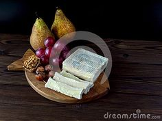 Brick shaped cheese with white mold, hazelnuts, walnut, red grape and pears on the textured wooden board