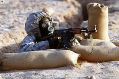 A Syrian soldier aims an TYPE (China made assault rifle from his position in a foxhole during a firepower demonstration, part of Operation Desert Shield. The soldier is wearing a Soviet-made Model ShMS nuclear-biological-chemical warfare masks. Ak 47, Urban Survival, Survival Guide, Survival Skills, Kalashnikov Rifle, Operation Desert Shield, Syrian Civil War, Chemical Weapon, Assault Rifle