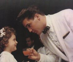 ♡♥Elvis Presley 26 in a pink suit with a bow tie gives a pink drink to a young lady at Red West's wedding on July 1st,1961♥♡