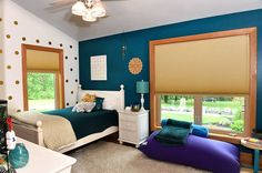 Teen bedroom with blue wall and white and gold polka dot wall.