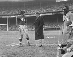 New York Giant's football coach Steve Owen on the sidelines talking to player Tom Landry.
