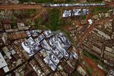 JR takes photos of the world's forgotten people and plasters them all over public spaces.  This one, 28 Millimeters, is part of his Women are Heroes series and hangs in the Kibera Slum in Kenya.  No one understood why the people in the upper right hand corner didn't have eyes... until the train pulled in.