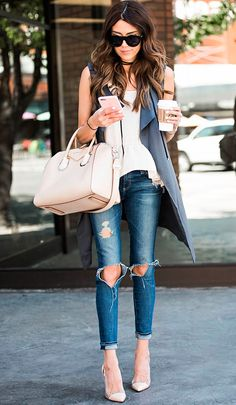 Street style look com colete, blusa branca, calça jeans e sapato nude.