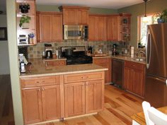 Hickory kitchen cabinets with granite countertops with short size suitable for small room large stainless steel refrigerator wood floor laminating granite material electric stove coffee maker large wooden cupboards shelf forkitchen tools ornaments kitchen sink stainless steel medium window large curtain unique ceramic orders on wall