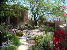 This flagstone walkway is located in a front yard. It allows people to explore the front garden, which includes a small patio, a water feature and low-water plants.