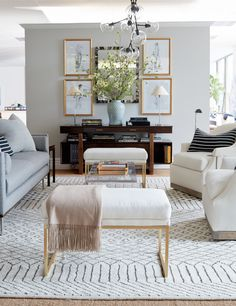 Stripes on the floor and stripes on throw pillows frame this gray and white living room perfectly.