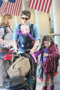 Maggie Gyllenhaal has her hands full as she carts her kids and luggage through LAX in Los Angeles #ergobaby #babywearing