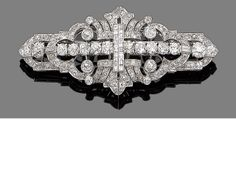 A diamond double clip brooch, circa 1930 The geometric pierced plaque set throughout with old brilliant-cut diamonds, highlighted with baguette and square-cut diamonds