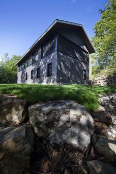 The pitched metal roof and dark-stained eastern cedar shingles ground the building in the lush surrounding landscape.