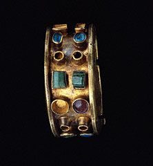 "300-400 AD Roman gold, glass, emerald (missing pearls) hinged bangle bracelet; 1 1/4"" x 2 1/2"" x 2 7/8""; Getty 83.AM.227.1. Per Getty: heavy gold band w/ colored stones & glass; made in 2 pieces, which were hinged & secured with pin decorated with green glass; edges folded perpendicularly out, forming ledge to protect stones: blue, green, red glass; emeralds; missing pearls; stones in pairs in simple gold settings. Shape is Roman, but design resembles jewelry from ""edges"" of Roman Empire…"