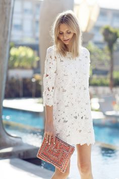 Shop this look on Lookastic:  https://lookastic.com/women/looks/white-lace-shift-dress-red-embroidered-clutch/10941  — Red Embroidered Clutch  — White Lace Shift Dress