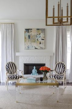 Stunning living room features a pair of French zebra chairs and a lucite and brass coffee table placed in front of a white fireplace and hearth accented with a gray and blue abstract art piece by Michelle Tulis. White Mantel, White Fireplace, Brick Fireplace, Formal Living Rooms, Living Room Decor, Grey Sofa Set, Zebra Chair, Shoji White, Blue Velvet Dining Chairs
