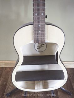 My family has always been pretty big into music, which is probably why I love to restore them. If you haven't seen my popular piano redo, click here to check it out. So I've been wanting to make a shelf out of a guitar for a while and decided to put a add up on an online yard sale site to see if I could purchase an incredibly cheap guitar. I wasn't picky because I wanted to best deal I could get. The one I purchased had the neck of the guitar starting to break off the body. It also had…