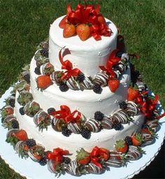 Round cake with three tiers and chocolate covered strawberries creating a ring around the base of each tier.